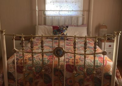 Queen size, Double bow front, Antique White with old fashioned porcelains and glass medallion, dressed with patchwork quilt.